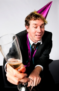 drunk man wearing crumpled suit and a party hat, holding a champagne glass.